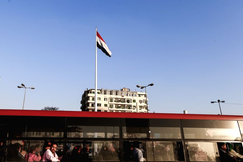 An Egyptian bus rider gives a V-sign as he passes by the symbolic Tahrir Square where a giant national flag of Egypt is seen flying at the top of a newly-installed ...