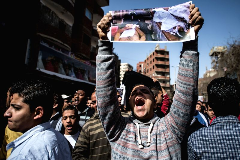 A man holds a photo showing bodies of killed football fans during a funeral of Mohamed Sayed, who died outside the Air Defense Stadium, in Cairo, Egypt, on Feb. 9, ... - Mohamed Sayed