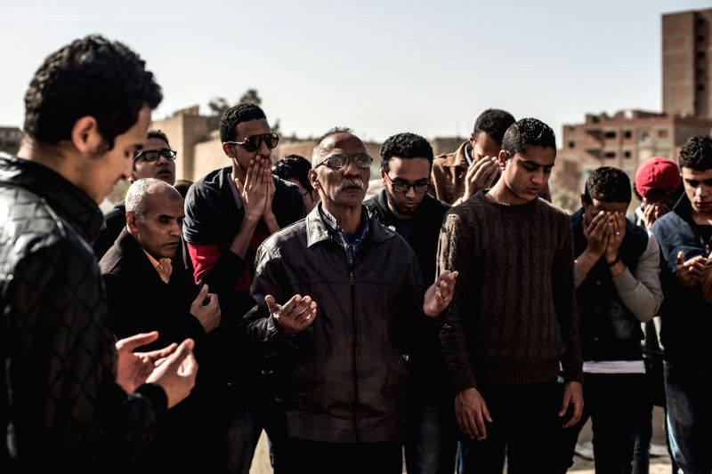 People pray for Mohamed Sayed, a football fan who died outside the Air Defense Stadium, at a cemetery in Cairo, Egypt, on Feb. 9, 2015. A total of 19 people were ... - Mohamed Sayed