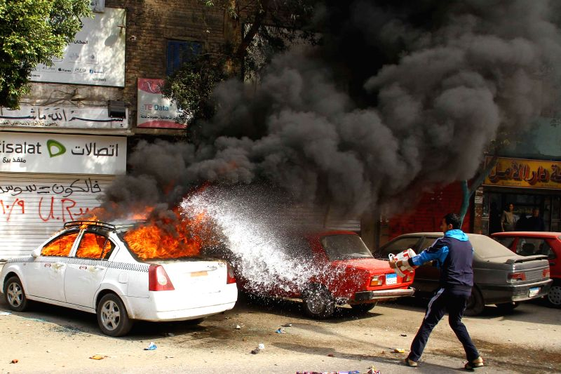 A man pours water to a car on fire set by supporters of Egypt's ousted President Mohamed Morsi in clashes with the police during a demonstration in the district of Al