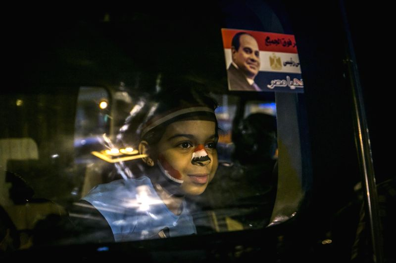 An Egyptian girl looks on during a public rally near Tahrir Square in Cairo, capital of Egypt, on Jan. 25, 2015. Sunday marks the fourth anniversary of an upheaval ...