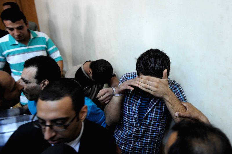 Men prosecuted of sexually assaulting on women hide their faces in Cairo, Egypt, July 16, 2014. An Egyptian court sentenced on Wednesday seven men to life in prison ..