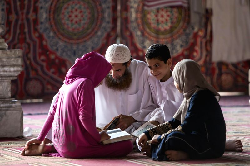 Egyptian children learn about Quran with their father inside a mosque during their fasting hours in a Ramadan afternoon in Cairo July 22, 2014.