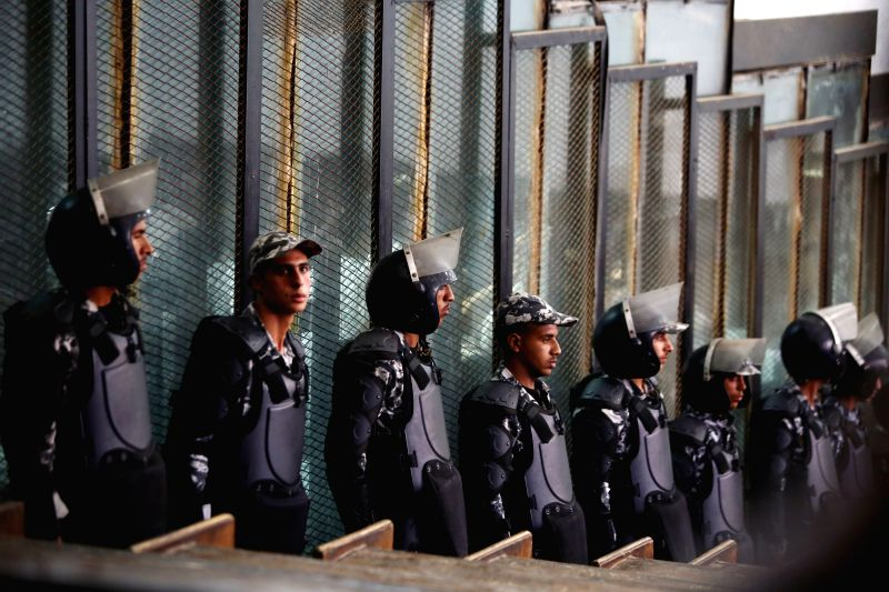 CAIRO, July 28, 2018 - Police officers stand in the court as suspects are seen behind a fence in Cairo, Egypt July 28, 2018. An Egyptian court on Saturday sentenced 75 members of the outlawed Muslim ...