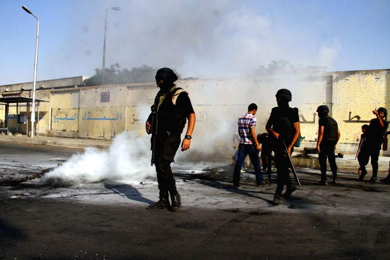Egyptian riot policemen douse burning tyres thrown by supporters of the deposed President Mohamed Morsi during their protest in Ain shams neighborhood, east Cairo, ...