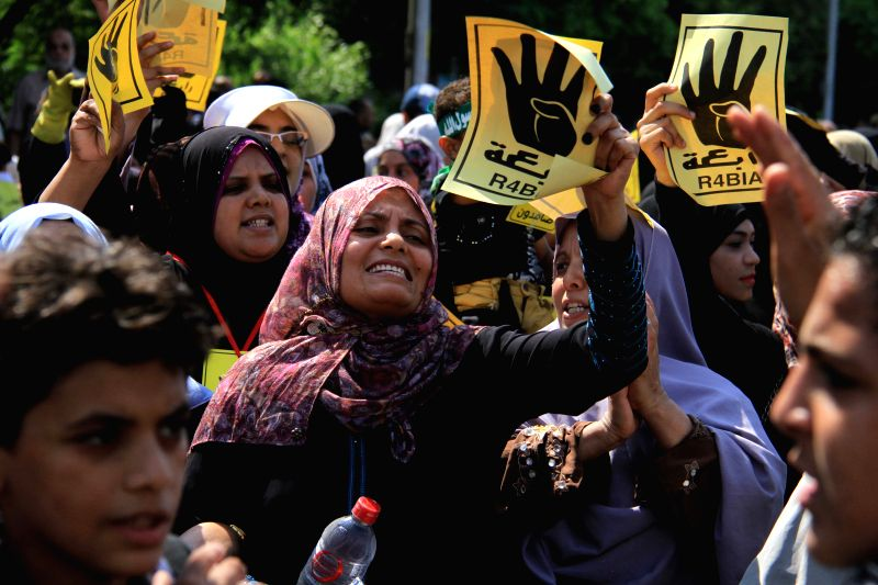 Supporters of the deposed President Mohamed Morsi take part in a demonstration in Ain shams neighborhood, east Cairo, Egypt, July 3, 2014. Morsi's supporters held ...
