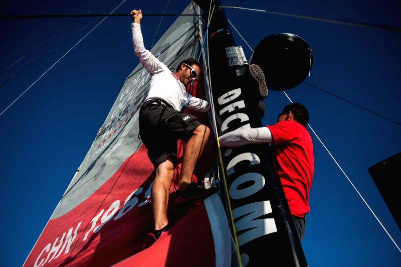 Eric Peron (L), trimmer of Dongfeng Team climbs on the mast to help his teammates to hoist the mainsail during the offshore training in the Bay of Biscay, western ...