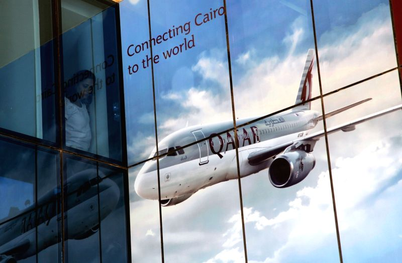 CAIRO, June 6, 2017 - A woman looks out from a window next to a ticket office of Qatar Airways in Cairo, Egypt on June 6, 2017. Egyptian Civil Aviation Ministry decided Monday to suspend flights to ...