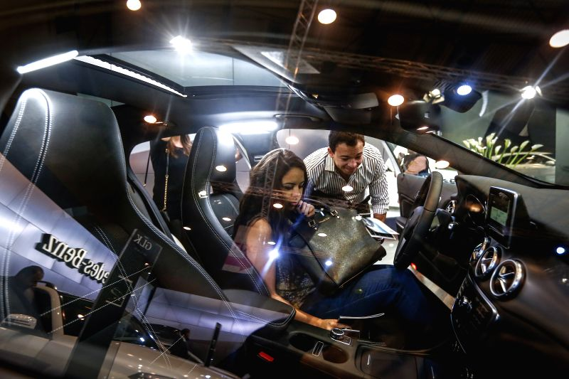 A woman sits in a displayed Mercedes sedan at the motor show in Cairo, Egypt, March 12, 2015. The 22nd Cairo International Motor Show opened here on Thursday. ...