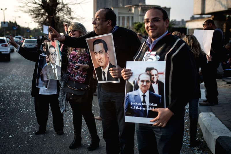 Supporters of Egypt's former President Hosni Mubarak hold his posters in front of Maadi Armed Forces Hospital where he is put under house arrest in Cairo, Egypt, on ...