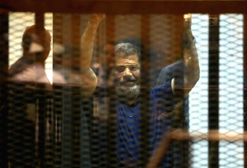 Egypt's ousted President Mohamed Morsi waves hands in the defendants' cage on a court in Cairo, Egypt, on May 16, 2015. An Egyptian court sentenced Saturday ousted ...