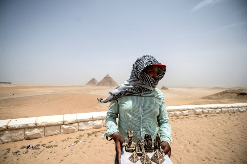 An Egyptian vendor waits for tourists in front of Giza Pyramids near Cairo, Egypt, on May 27, 2015. Hot weather with sandstorm hit Egypt on Wednesday, and the ...
