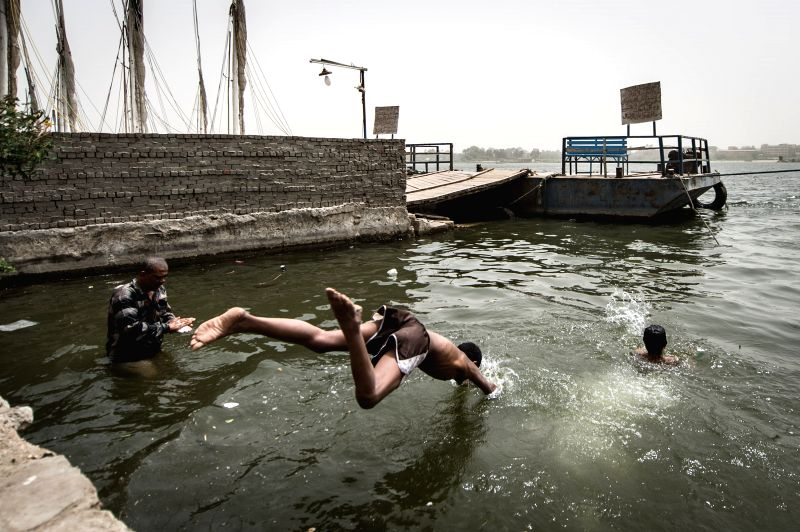 Egyptian fishermen dive into the Nile River in Cairo, Egypt, on May 27, 2015. Hot weather with sandstorm hit Egypt on Wednesday, and the temperature reached 44 degree ...