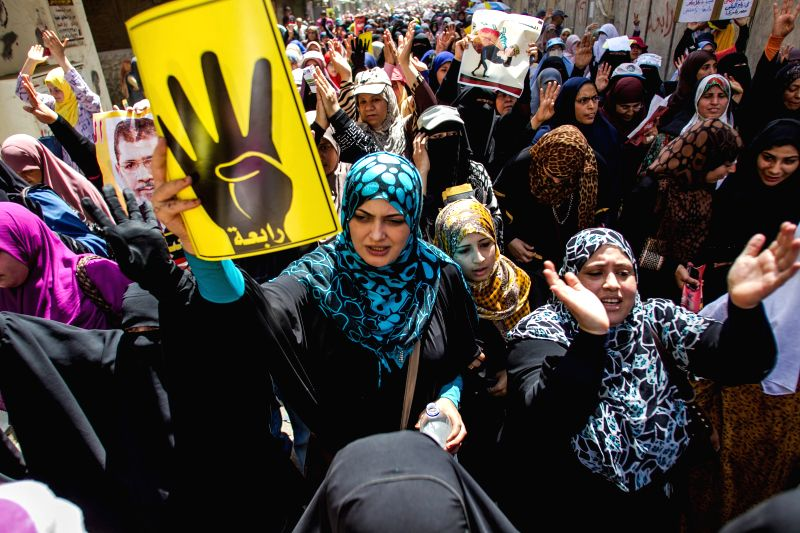 Anti-military protesters shout slogans and gesture the four-finger salute during a demonstration in Al-Matareya neighborhood in Cairo, Egypt, May. 2, 2014. ...