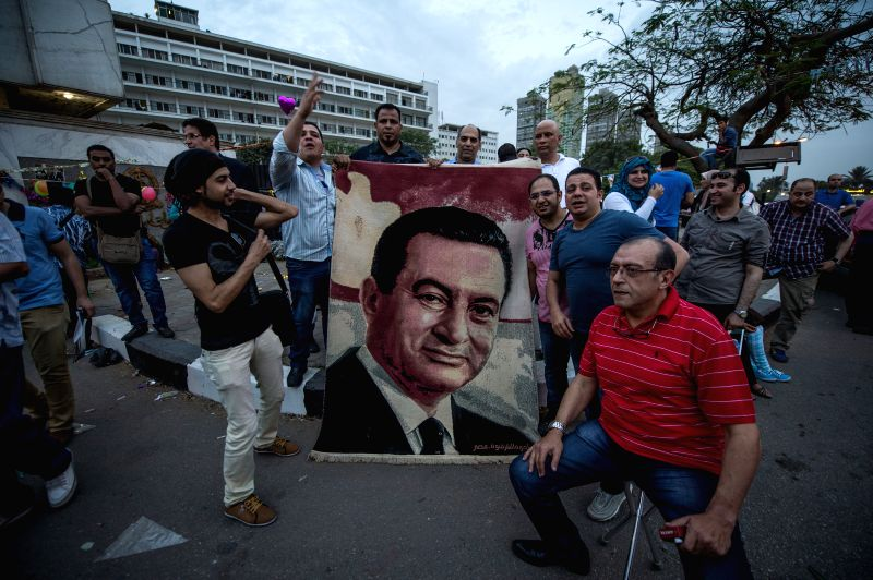 Egyptians pose with a giant portrait of Egypt's former president Hosni Mubarak  for celebrating his 86th birthday in front of Maadi Armed Forces Hospital where Mubarak .