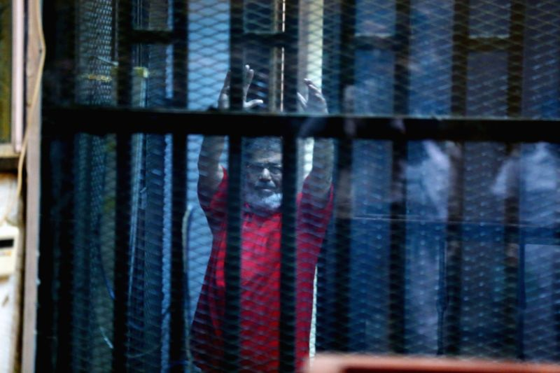 CAIRO, May 7, 2016 - Egypt's ousted President Mohamed Morsi gestures behind the defendants' cage at a court during his trial in Cairo, Egypt on May 7, 2016. An Egyptian Court on Saturday sentenced to ...