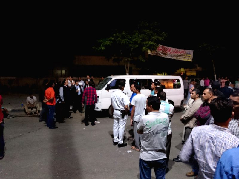CAIRO, May 8, 2016 - People stand around a police minivan in the Helwan district in south Cairo, capital of Egypt, May 8, 2016. Four gunmen attacked the vehicle and shot dead eight policemen in the ...