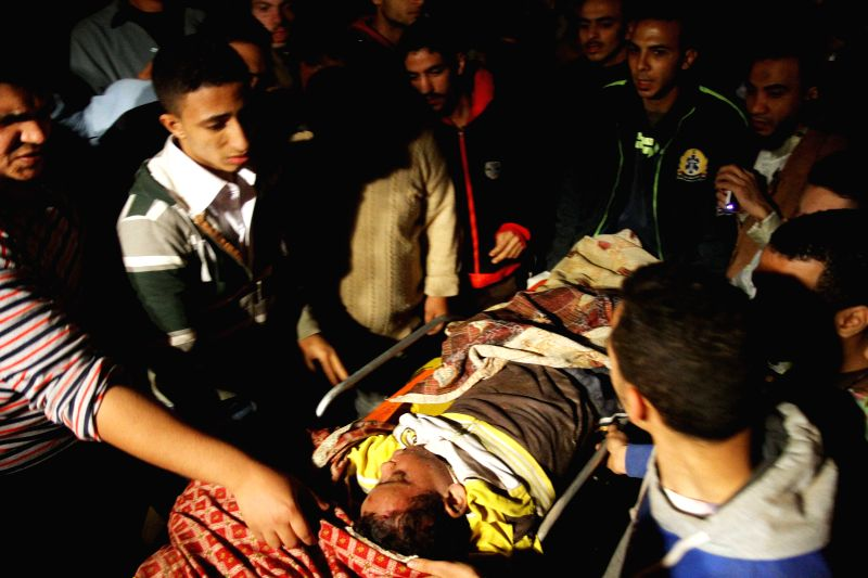 People transfer an injured man at the site of a collapsed building in northeast Cairo, Egypt, Nov. 25, 2014. At least 11 people died and seven others were injured when a building collapsed in .