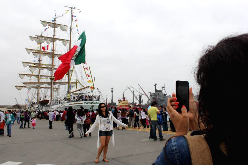 "A resident takes photos in front of the sailboat ""Cuauhtemoc"" of Mexico during the Latin America Sails 2014 regatta at the Naval Base in Callao, Peru, ..."