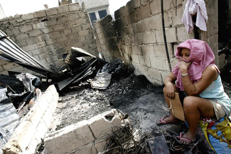 A resident rests beside her burnt house after a fire hit a slum area in Caloocan City, the Philippines on April 21, 2014. Around 1,000 families were affected