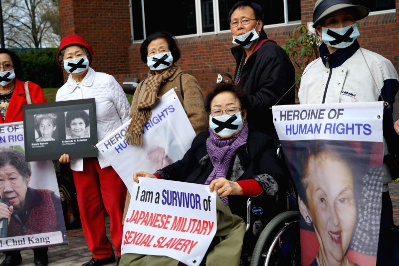 Dozens of protesters hold signs and posters urging visiting Japanese Prime Minister Shinzo Abe to look squarely at history and apologize for the crimes committed ... - Shinzo Abe