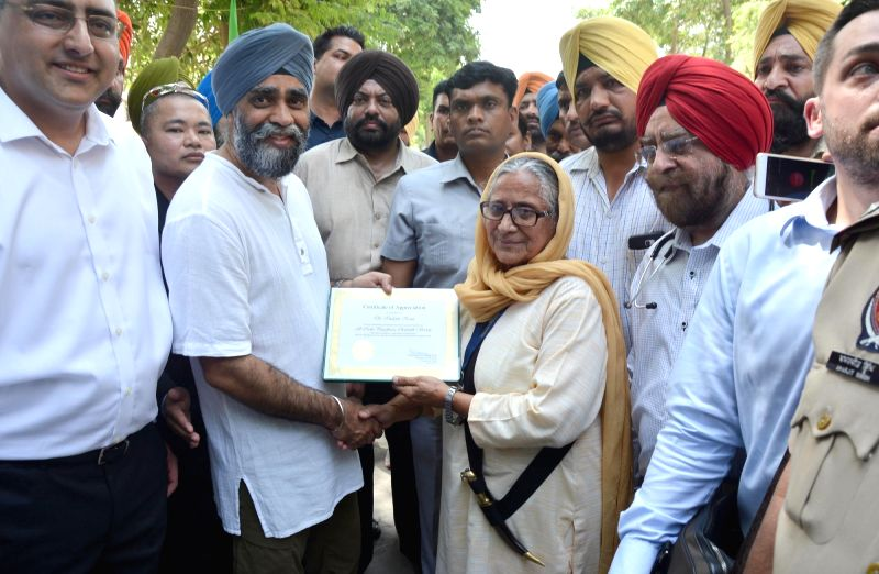 Canadian Defence Minister Harjit Singh Sajjan receives a certificate of appreciation from the founder of Pingalwara Dr. Inderjit Kaur during his visit to Pingalwara in Amritsar on April 20, ... - Harjit Singh Sajjan and Inderjit Kaur