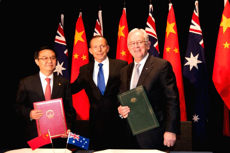China's Commerce Minister Gao Hucheng (L) and Australia's Trade Minister Andrew Robb (R) pose for photos with Australian Prime Minister Tony Abbott after signing ... - Gao Hucheng