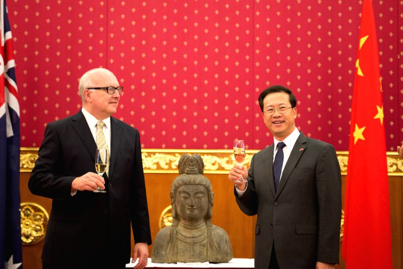 Chinese ambassador to Australia Ma Zhaoxu (R) and Australia's Minister for the Arts Senator George Brandis celebrate with champagne after signing and exchanging ...