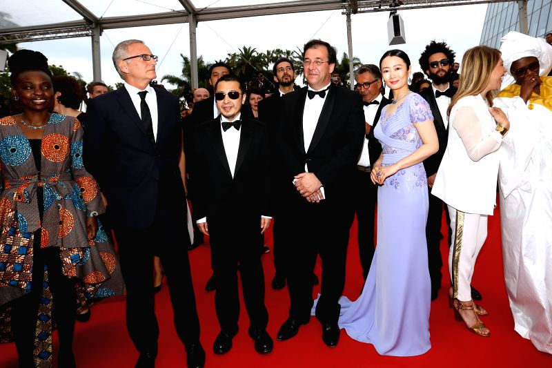"""CANNES, May 14, 2016 - Chinese director Jia Zhangke (3rd L) and his wife, actress Zhao Tao (5th L) pose on the red carpet as they arrive for the screening of the film """"Ma loute"""" (Slack Bay) ... - Jia Zhangke"""