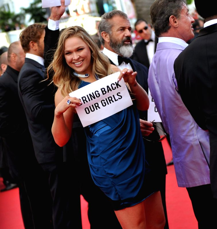 """Actress Ronda Rousey of """"The Expendables 3"""", holding up banners reading """"Bring back our girls"""", part of a campaign calling for the release of the"""