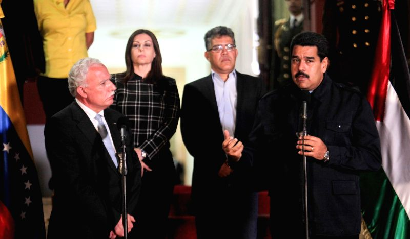 Venezuela's President Nicolas Maduro (1st R) delivers a speech during his meeting with Palestinian Foreign Minister Riad al-Malki (1st L) in Miraflores Palace, in ..