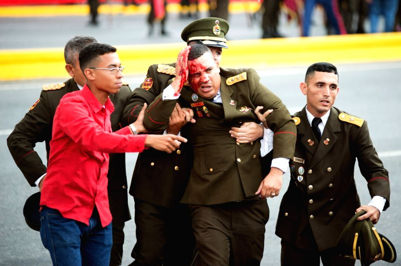CARACAS, Aug. 4, 2018 - A security member bleeds after Venezuelan President Nicolas Maduro's speech was interrupted in Caracas, Venezuela, on Aug. 4, 2018. Venezuela's Minister of Communication Jorge ...
