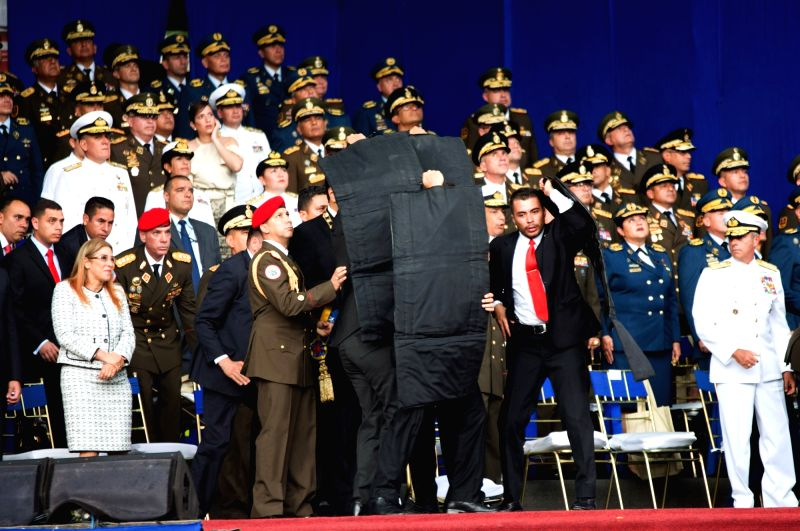 CARACAS, Aug. 4, 2018 - Security members protect Venezuelan President Nicolas Maduro after his speech was interrupted in Caracas, Venezuela, on Aug. 4, 2018. Venezuela's Minister of Communication ...