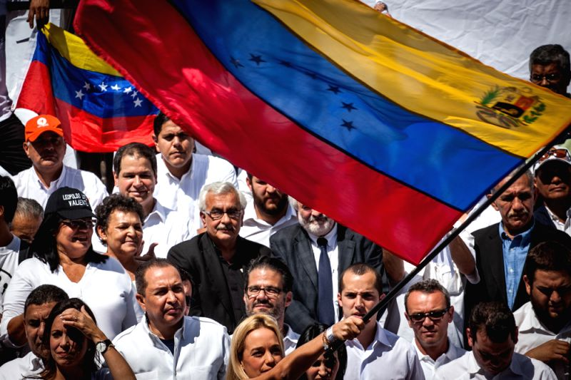 Lilian Tintori (C, front), wife of jailed opposition leader Leopoldo Lopez, waves a national flag during a march in support of Leopoldo Lopez, in Caracas, ...