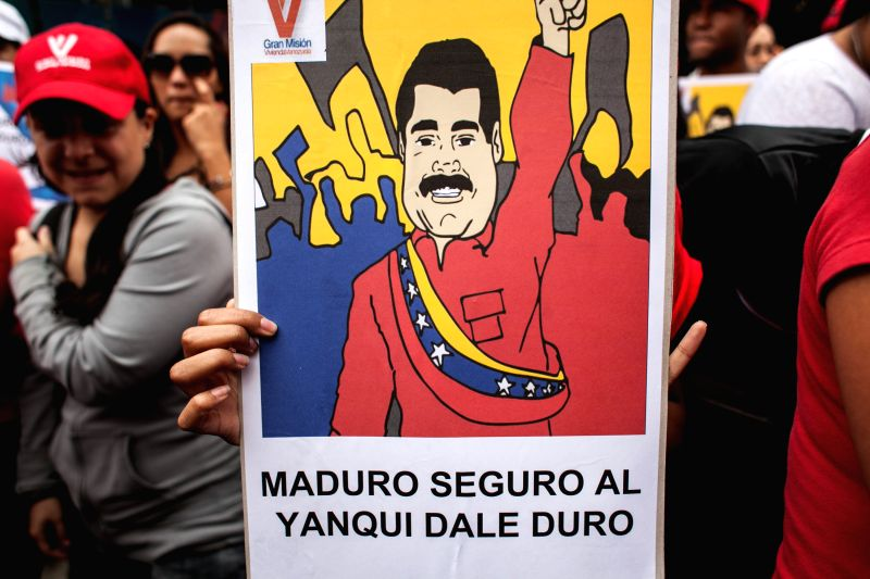 "A person holds a banner during an ""anti-imperialist"" march in Caracas, Venezuela, on March 12, 2015. Residents in Caracas and other regions of Venezuela ..."