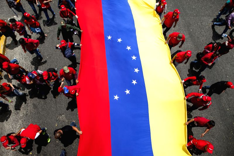 Oil workers hold a national flag during a rally in Caracas, Venezuela, March 18, 2015. Venezuelan President Nicolas Maduro said on Wednesday that his government ...