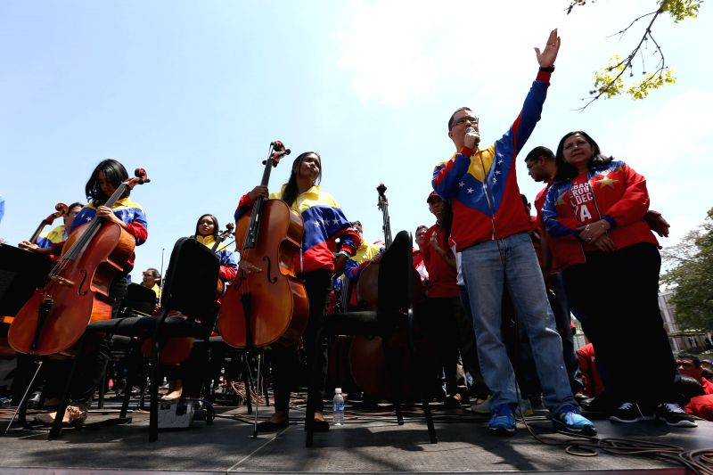 People take part in an event, headed by Venezuela's Vice President Jorge Arreaza (2nd R, front), to collect signatures for a petition against the executive order ...