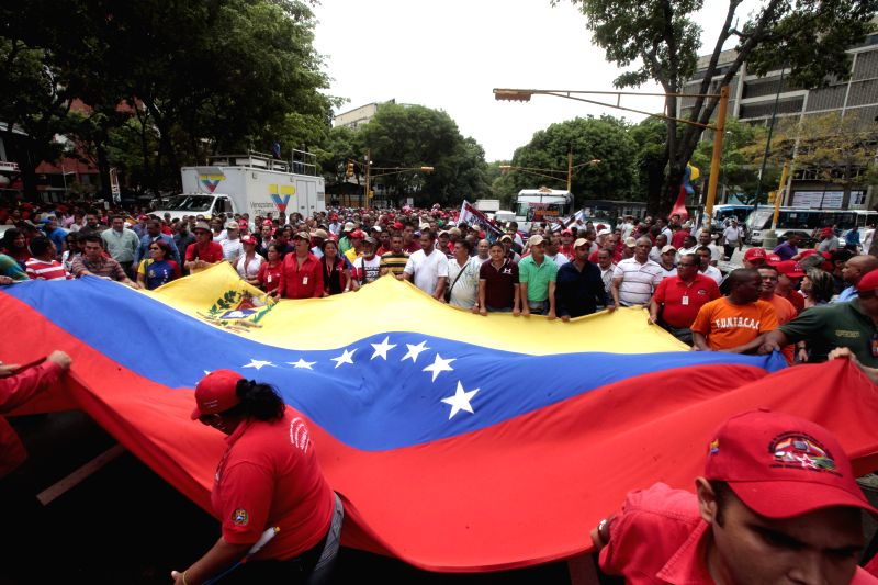 People hold a national flag during a march in Caracas, Venezuela, on May 12, 2014. Employees of the Caracas subway, along with representatives of the Bolivarian ...