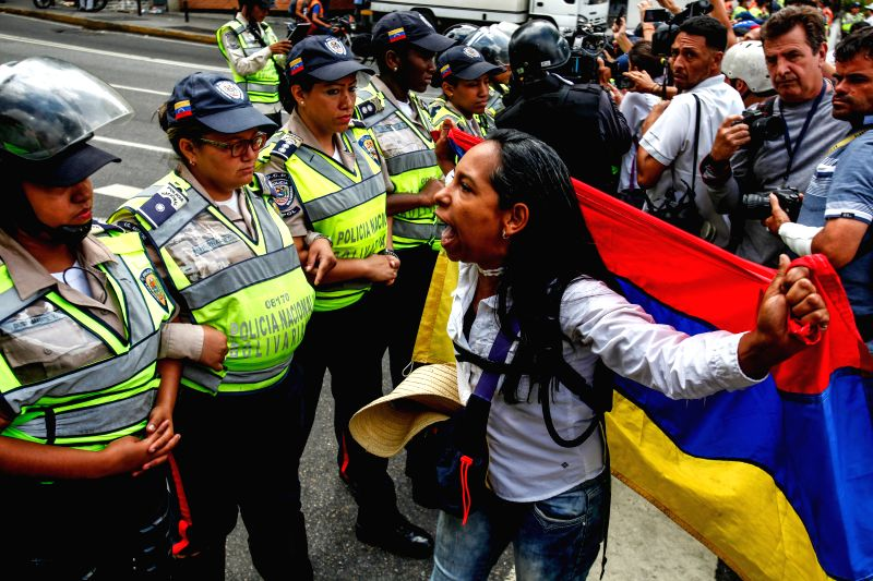 CARACAS, May 7, 2017 - A demonstrator reacts in front of members of the National Bolivarian Police during a rally organized by female supporters of the opposition in Caracas, Venezuela, on May 6, ...