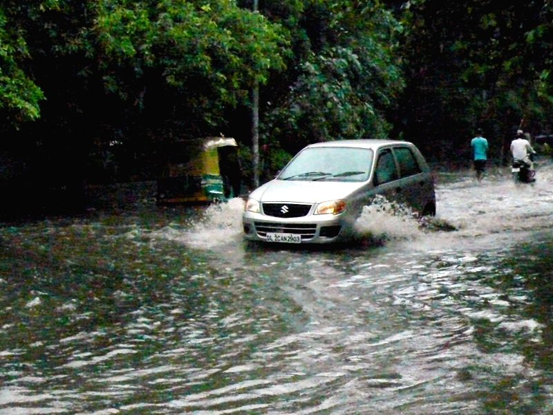 Cars parked in a water logged parking  after a heavy downpour in New Delhi on July 26, 2018.