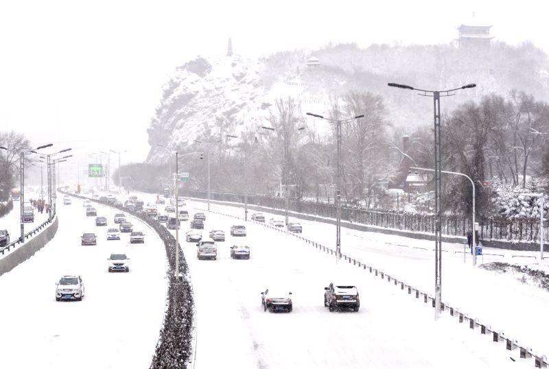 Cars run in snow in Urumqi, capital of northwest China's Xinjiang Uygur Autonomous Region, Dec. 11, 2015. A snowstorm hit Urumqi on Dec. 11 and the local ...