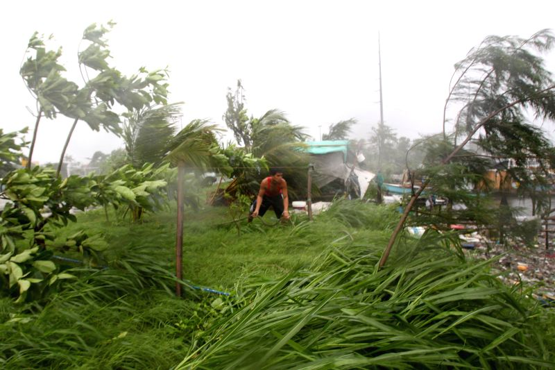 A man holds on a rope as he braves the strong winds from typhoon Rammasun in Cavite Province, the Philippines, July 16, 2014. At least 5 people were killed .