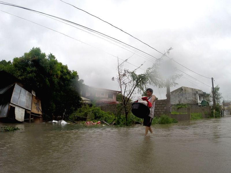 A man wades on flood brought by typhoon Rammasun in Cavite Province, the Philippines, July 16, 2014. At least 5 people were killed following the onslaught ..