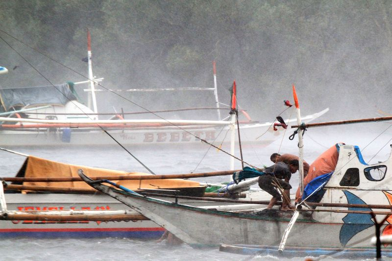 Fishermen try to secure their boat as they brave the strong winds from typhoon Rammasun in Cavite Province, the Philippines, July 16, 2014. At least 5 ...