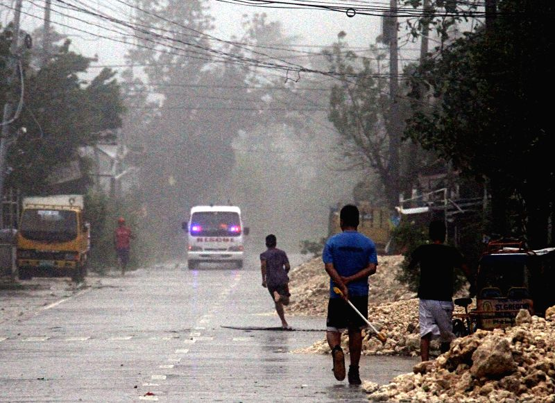 Cebu (Philippines): Residents run for safety due to strong winds and heavy rains brought by typhoon Hagupit in Cebu Province, the Philippines, Dec. 7, 2014. More than 896,000 people were served ...