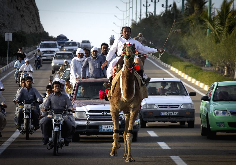 An Iranian man takes part in a camel running competition at port city of Chabahar, southeastern Iran, on March 6, 2015.