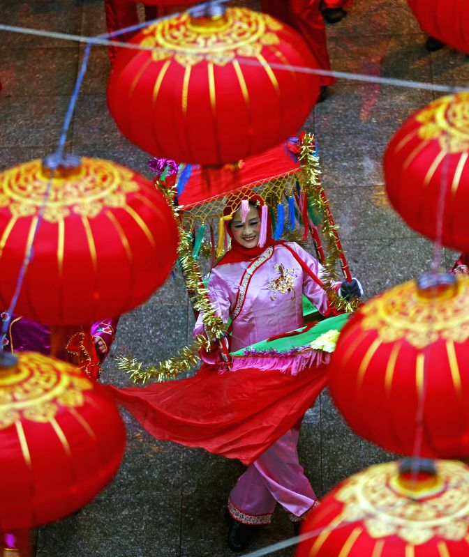 A performer takes part in a parade to celebrate the Lantern Festival in Changsha, capital of central China's Hunan Province, March 5, 2015. The festival, which ...