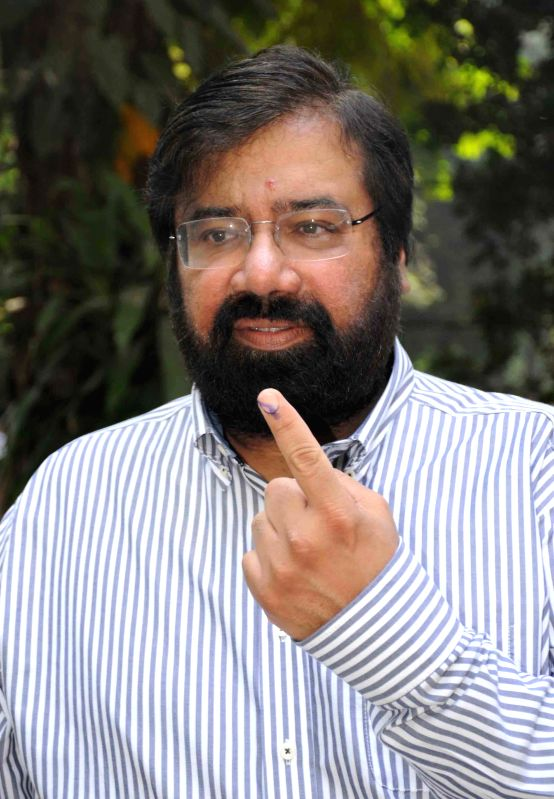 Chairman of RPG Enterprises Harsh Goenka shows his fore finger marked with phosphorous ink after casting his vote at a polling booth during the sixth phase of 2014 Lok Sabha Polls in Mumbai on April .