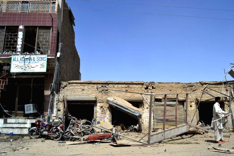 CHAMAN, Aug. 7 A man stands near destroyed shops at the bomb blast site in southwest Pakistan's Chaman on Aug. 7, 2014. Eleven people, including three policemen, were injured when a bomb .
