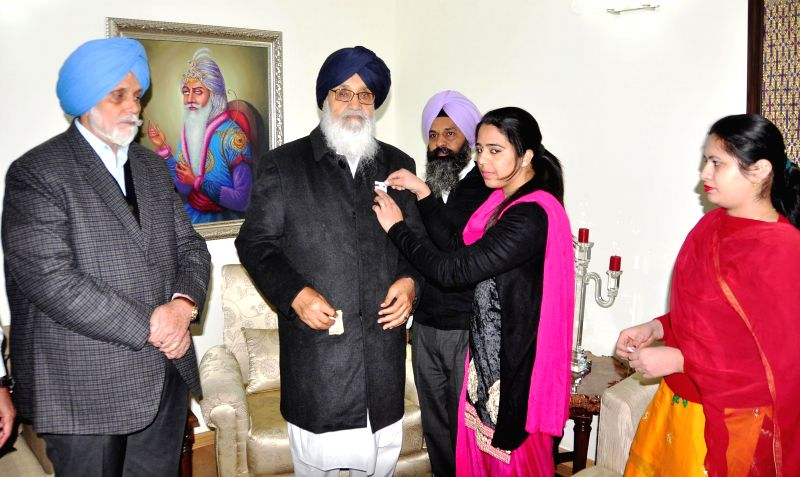 A volunteer pins a flag on Punjab Chief Minister Parkash Singh Badal on the occasion of the Flag Day in Chandigarh on Dec 10, 2014. - Parkash Singh Badal